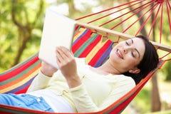 Frau, die in der Hängematte mit E-Buch sich entspannt Stockbilder