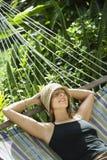 Frau, die in der Hängematte sich entspannt. Stockfotografie
