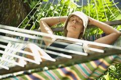 Frau, die in der Hängematte sich entspannt. stockbilder