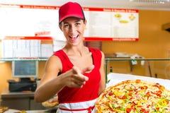 Frau, die in der Hand eine ganze Pizza anhält Lizenzfreie Stockbilder