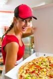 Frau, die in der Hand eine ganze Pizza anhält Stockbild