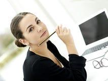 Frau, die in der Hand Kamera mit Bleistift betrachtet Stockfotografie