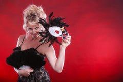 Frau, die in der Hand Karnevalsmasken-Federfan hält Stockfotos