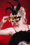 Frau, die in der Hand Karnevalsmasken-Federfan hält Stockfotografie