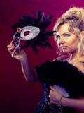 Frau, die in der Hand Karnevalsmasken-Federfan hält Stockfoto