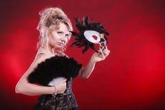 Frau, die in der Hand Karnevalsmasken-Federfan hält Lizenzfreie Stockfotos