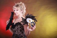 Frau, die in der Hand Karnevalsmasken-Federfan hält Lizenzfreie Stockbilder