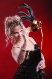 Frau, die in der Hand Karnevalsmasken-Federfan hält Lizenzfreies Stockbild