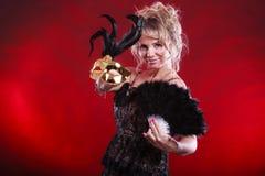 Frau, die in der Hand Karnevalsmasken-Federfan hält Lizenzfreie Stockfotografie