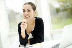 Frau, die in der Hand mit Bleistift lächelt Lizenzfreies Stockfoto
