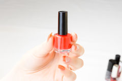 Frau, die in der Hand roten Nagellack mit der Nagelkunst an lokalisiert hält Lizenzfreie Stockfotos