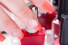 Frau, die in der Hand roten Nagellack mit der Nagelkunst an lokalisiert hält Lizenzfreie Stockfotografie