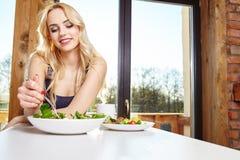 Frau, die in der Küche frühstückt lizenzfreie stockfotos