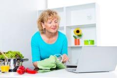 Frau, die in der Küche kocht und Computer verwendet Lizenzfreies Stockfoto