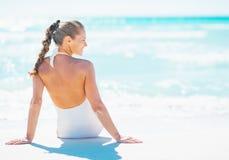 Frau, die an der Küste sitzt und auf Kopienraum schaut Stockfoto