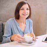 Frau, die an der Kamera mit Kaffee in ihren Händen lächelt Lizenzfreie Stockfotografie