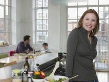 Frau, die an der Küchenarbeitsplatte mit Familie im Hintergrund steht Lizenzfreie Stockbilder
