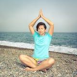 Frau, die an der Küste meditiert Stockbild