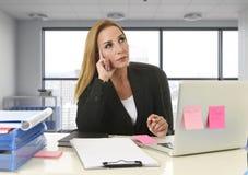 Frau, die an der Laptop-Computer sitzt auf um dem Schreibtischabwesenden gekümmerten und durchdachten Sitzen im Geschäftsgebietbe Stockfotografie