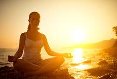 Frau, die in der Lotoshaltung auf dem Strand meditiert Lizenzfreie Stockbilder