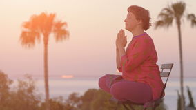 Frau, die in der Lotoshaltung bei Sonnenaufgang meditiert Gesunder Lebensstil Morgenmeditation Yoga-Meditations-Konzept Junge Fra stock video footage
