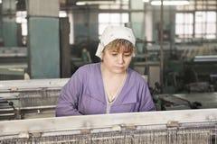 Frau, die an der Maschine arbeitet Stockbild
