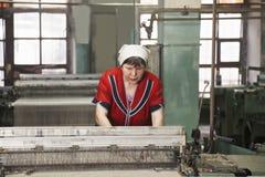 Frau, die an der Maschine an der Fabrik arbeitet lizenzfreies stockfoto