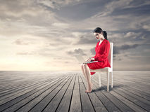 Frau, die in der Mitte von Nirgendwo sitzt Lizenzfreie Stockfotografie