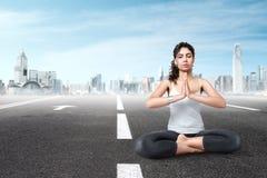 Frau, die in der modernen Stadt meditiert Stockfotos