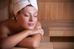 Frau, die in der Sauna sich entspannt Stockfotografie