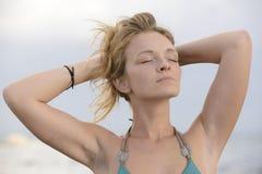 Frau, die in der Sonne auf dem Strand sich entspannt Stockfotos