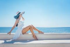 Frau, die in der Sonne auf einem griechischen Strand sitzt Lizenzfreie Stockbilder