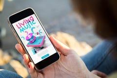 Frau, die in der Straße hält ihre Smartphonegrasenlebenmusikwebsite sitzt lizenzfreies stockfoto