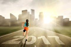 Frau, die an der Straße mit 2017 läuft Lizenzfreies Stockfoto