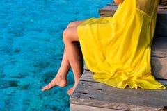 Frau, die an der Strandanlegestelle sitzt lizenzfreie stockfotografie