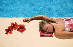 Frau, die an der Swimmingpoolseite sich entspannt Lizenzfreie Stockfotografie