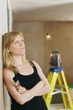 Frau, die an der Wand mit Leiter hinten sich lehnt Stockbilder