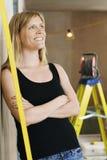 Frau, die an der Wand mit Leiter hinten sich lehnt Lizenzfreie Stockfotografie
