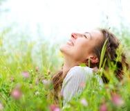 Frau, die in der Wiese der Blumen liegt Stockbilder