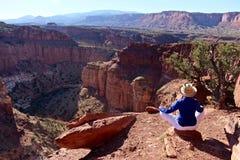 Frau, die in der Yoga-Haltung am Rand der Schlucht meditiert Stockbilder