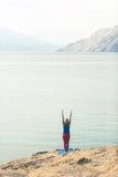 Frau, die in der Yogabaumhaltung am Meer und an den Bergen meditiert Stockbild