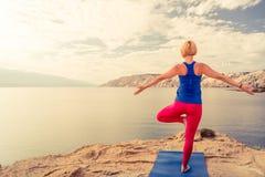Frau, die in der Yogabaumhaltung am Meer und an den Bergen meditiert Lizenzfreie Stockfotos