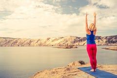 Frau, die in der Yogabaumhaltung am Meer und an den Bergen meditiert Lizenzfreie Stockbilder