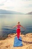 Frau, die in der Yogabaumhaltung am Meer und an den Bergen meditiert Lizenzfreie Stockfotografie