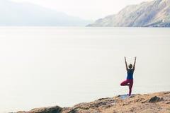 Frau, die in der Yogabaumhaltung am Meer und an den Bergen meditiert Lizenzfreies Stockbild