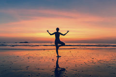 Frau, die an der Yogahaltung auf dem Strand während des fantastischen Sonnenuntergangs steht Lizenzfreies Stockfoto