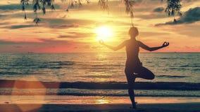Frau, die an der Yogahaltung auf dem Strand während eines erstaunlichen Blutsonnenuntergangs steht Stockfotos