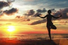 Frau, die an der Yogahaltung auf Strand während des erstaunlichen Sonnenuntergangs steht Stockfotografie