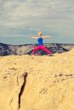 Frau, die in der Yogahaltung am Meer und an den Bergen meditiert Lizenzfreie Stockfotografie
