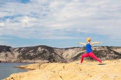 Frau, die in der Yogahaltung am Meer und an den Bergen meditiert Lizenzfreies Stockfoto